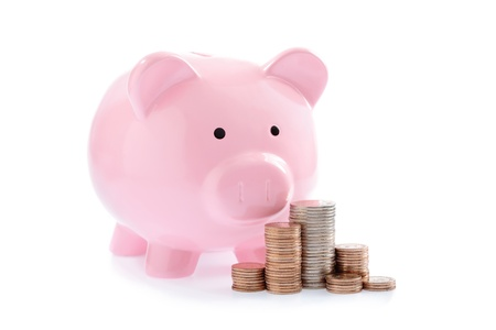 Pink piggy bank and Stacks of money coins isolated over the white background photo