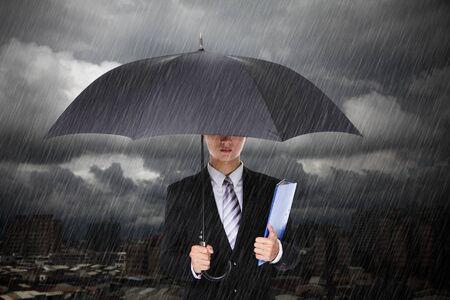 uomo sotto la pioggia: Uomo d'affari sotto la pioggia con nuvole tempesta e città sfondo