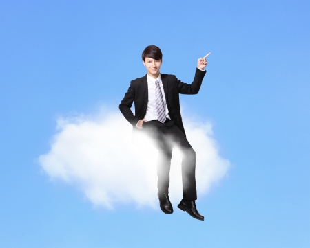 business man sitting on a cloud and finger point to empty copy space over blue sky in full length, asian male model photo