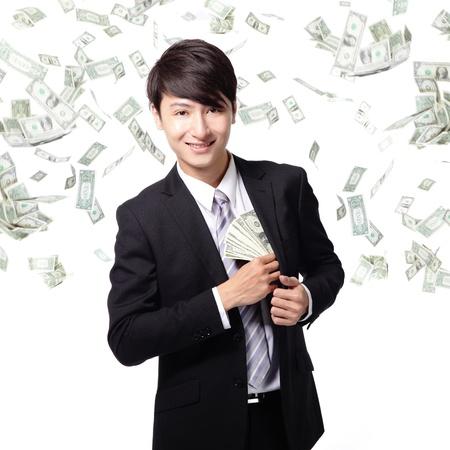 sotto la pioggia: felice l'uomo d'affari con il dollaro guadagnato noi soldi in tasca tuta sotto una pioggia di denaro - isolato su uno sfondo bianco, modello asiatico