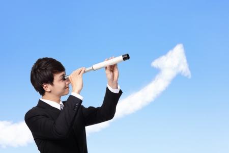 investment solutions: joven hombre de negocios contra el cielo azul se ve a trav�s del telescopio con el crecimiento de cloud flecha. un s�mbolo de liderazgo, el �xito y la libertad. Foto de archivo