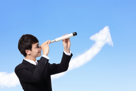 young business man against the blue sky looks through a telescope with growth arrow cloud. a symbol of leadership, success and freedom. photo