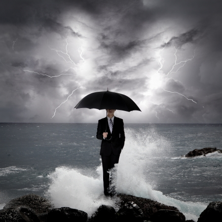 savings risk: Business man under an umbrella standing on a rock in the sea with lightning sky, business concept Stock Photo