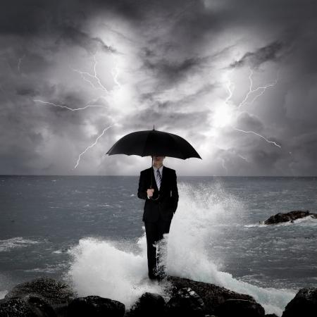 lluvia paraguas: Hombre de negocios bajo el paraguas de pie sobre una roca en el mar con el cielo un rayo, concepto de negocio Foto de archivo