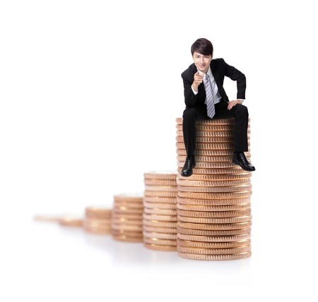Successful business man sitting on money stairs coin and point to you with smile isolated against white background, asian male model photo
