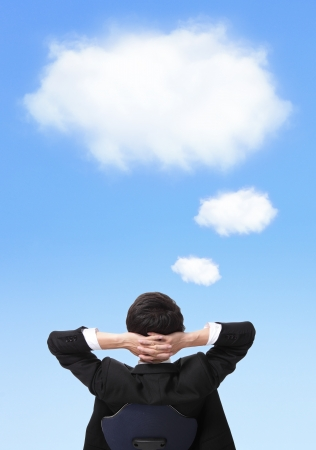 blue sky thinking: Rear viwe of a relaxed businessman with hands behind his head Stock Photo