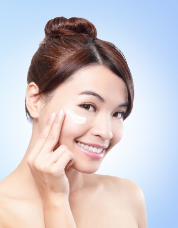 Close up young beautiful face of girl applying moisturize cream or sunblock lotion - isolated on blue background, asian beauty photo
