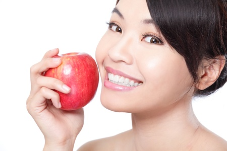 Portrait of lovely young woman holding a fresh ripe apple and smiling with health teeth isolated on white background, asian beauty photo