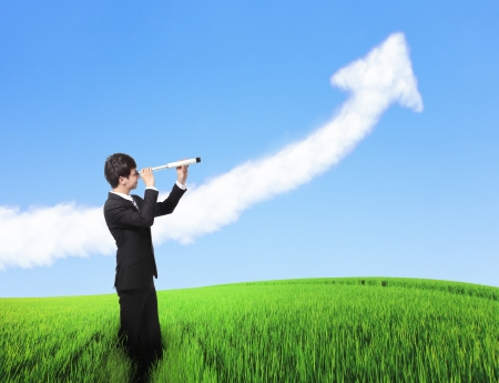 business man looks through a telescope with growth arrow cloud with green grass and blue sky. concept for business, leadership, success, ECO and freedom photo