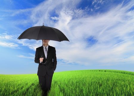 Risk Free: serious business man standing oh the green field and holding black umbrella, concept for business