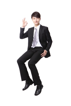 okey: Successful business man sitting on something and show ok hand sign isolated against white background, asian male model Stock Photo