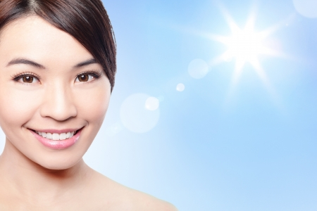 Beautiful woman face with sunshine and blue sky, concept for summer skin care and sun block, asian beauty photo