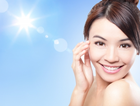 sun lotion: Beautiful woman face with sunshine and blue sky, concept for summer skin care and sun block, asian beauty Stock Photo