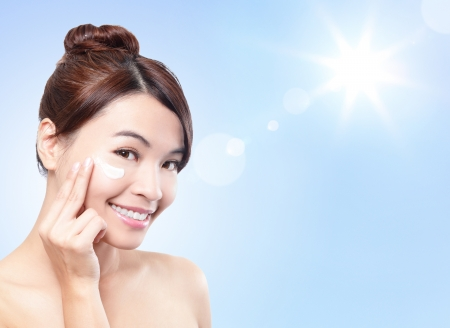 sunblock: Beautiful woman face with sunshine and blue sky, concept for summer skin care and sun block, asian beauty Stock Photo