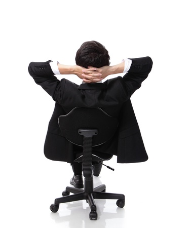 man in chair: Rear viwe of a relaxed businessman with hands behind his head and sit on a chair