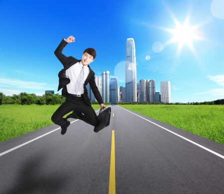 Excited Business man jump and run on the road with city background. concept for success business photo