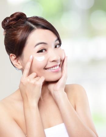mujer maquillandose: Belleza de la mujer joven de aplicar la crema cosmética bajo los ojos Foto de archivo