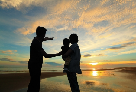 father with children: silhouette of family watching the sunrise on the beach