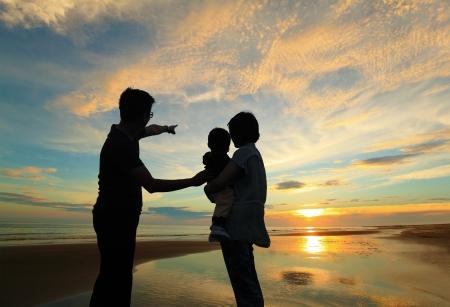 Silueta de la familia viendo la salida del sol en la playa Foto de archivo - 20022543