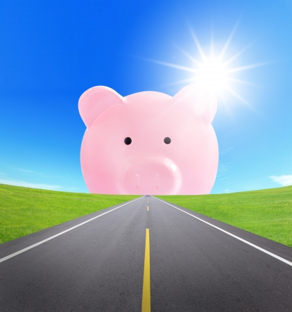 asphalt road to a pink piggy bank with cloudy sky and sunlight, business concept photo