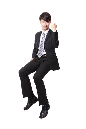 Successful business man sitting on something and show fist hand sign isolated against white background, asian male model photo