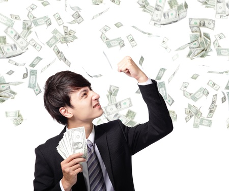 money risk: Excited business man earned dollar bills us money under a money rain - isolated over a white background, asian model Stock Photo