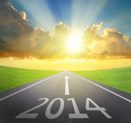 new way: Forward to 2014 new year concept , asphalt road with arrow , date and beautiful sunset and sunshine Stock Photo