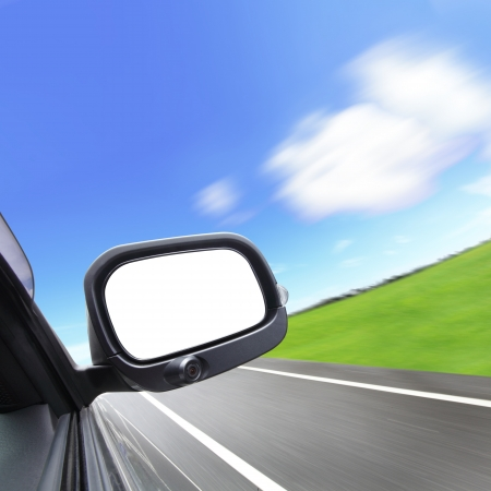 car and rear view mirror on the road photo