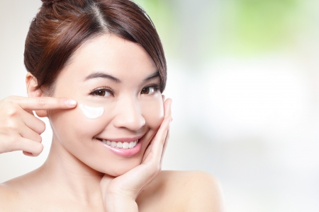 Beauty young woman applying cosmetic cream under eyes, concept for eye and skin care photo