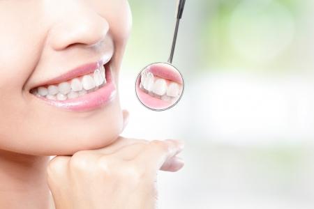 zuby: Zdravá žena zuby a zubař ústa zrcadlo s přírodním zeleným pozadím