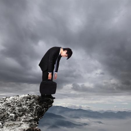 山の危険の絶壁、アジアの人々 のビジネスのための概念以上仕事から落ち込んで若いビジネス男
