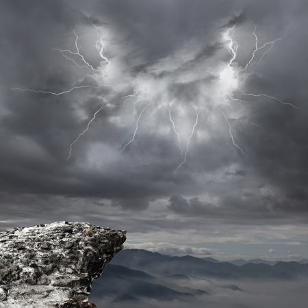 steep cliff: danger precipice on the mountain with rainstorm clouds and lightning Stock Photo