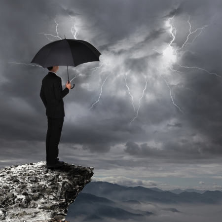 steep cliff: Business Man with an umbrella look rainstorm clouds and lightning over danger precipice on the mountain,  concept for business and insurance
