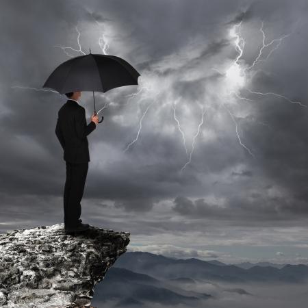 UOMO pioggia: L'uomo d'affari con un ombrello sguardo temporale nuvole e fulmini oltre pericolo precipizio in montagna, concetto per le imprese di assicurazione e di Archivio Fotografico