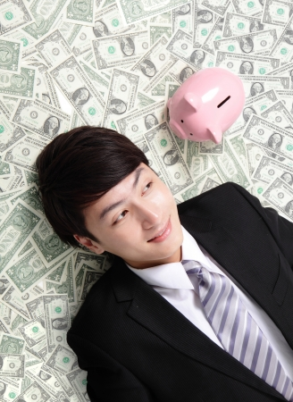 happy businessman look pink piggy bank and lying on money bed, asian man photo