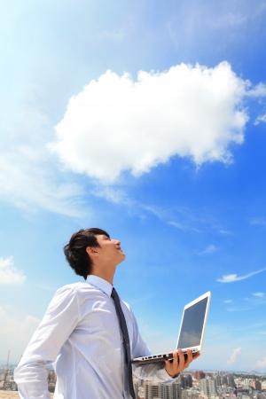hombre de negocios: Hombre de negocios joven usando la computadora portátil y mirar al cielo azul y las nubes con el paisaje urbano en el concepto de computación en el fondo, los negocios y la nube Foto de archivo