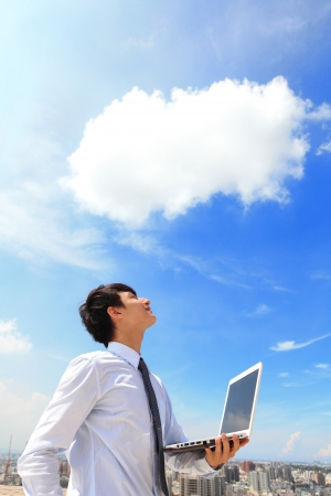 guy with laptop: Young business man using laptop and look to blue sky and cloud with cityscape in the background, business and cloud computing concept