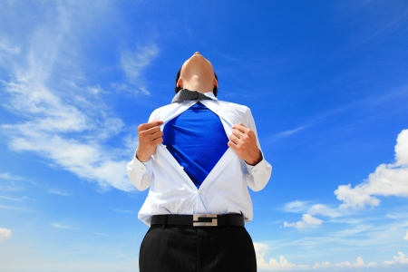 blue shirt: Business man pulling his t-shirt open, showing a superhero suit underneath his suit Stock Photo