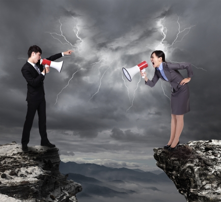 angry couple: business Man and woman shouting to each other through megaphone on danger precipice on the mountain with rainstorm clouds and lightning
