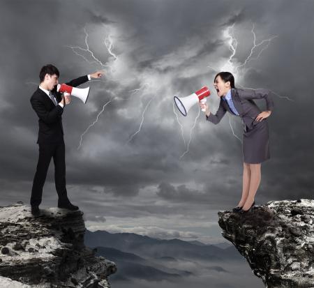 pareja enojada: Hombre de negocios y la mujer gritando el uno al otro a través del megáfono en peligro precipicio en la montaña con nubes temporal de lluvia y rayos