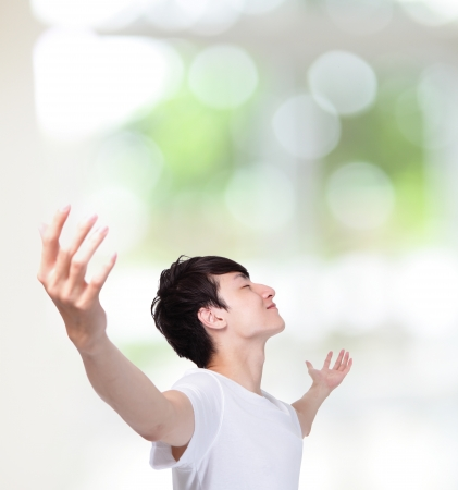 young man carefree outstretched arms with green background, healthy lifestyle concept, asian people