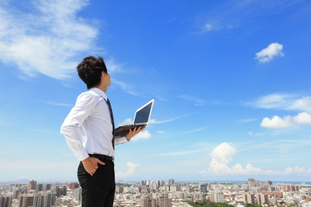 finding: Young business man using laptop and look to blue sky and cloud with cityscape in the background, business and cloud computing concept