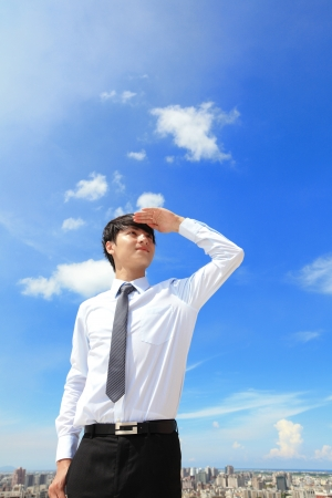 Successful handsome business man purposefully looking away with blue sky and city background, mode is a asian male Stock Photo - 20837140