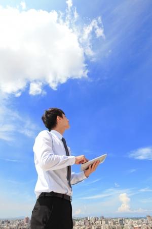 젊은 비즈니스 사람 (남자)는 태블릿 PC를 사용하고, 배경, 사업, 클라우드 컴퓨팅 개념의 풍경과 푸른 하늘과 구름을 바라
