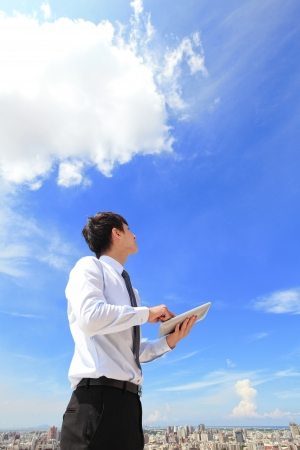 business connection: Young business man using tablet pc and look to blue sky and cloud with cityscape in the background, business and cloud computing concept