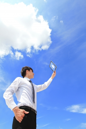 internet cloud: Young business man using tablet pc and look to blue sky and cloud with cityscape in the background, business and cloud computing concept