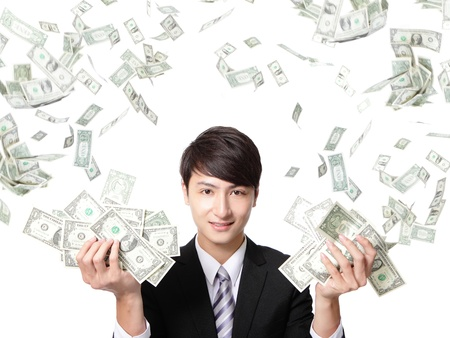 happy business man earned dollar bills us money under a money rain - isolated over a white background, asian model photo