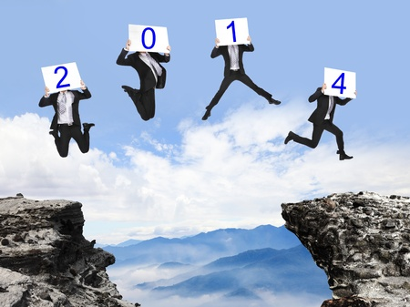background calendar: jump to 2014 year , businessman overcome danger precipice and jumping with 2014 text billboard on the mountain, concept for new year, asian people