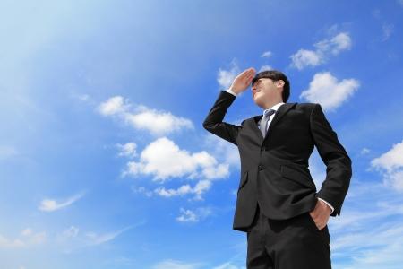 and future vision: Exitoso hombre de negocios atractivo mirando a otro lado a propósito con el cielo azul y el fondo de la ciudad