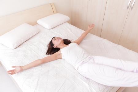 행복한 여자는 누워서 집에서 그녀의 침대에 점프